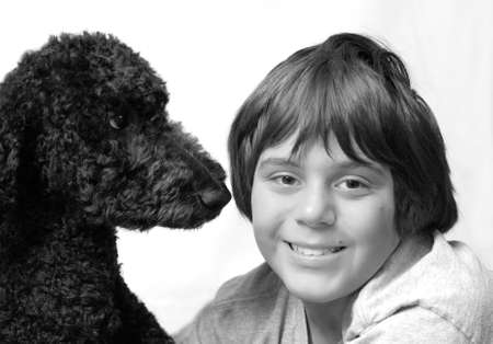 tender moment between twelve year old boy and his standard poodle dog photo
