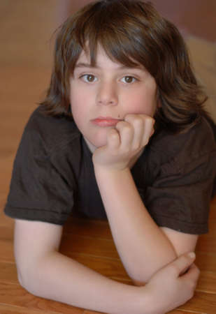 twelve year old boy with chin resting in hands and pensive expression on face photo