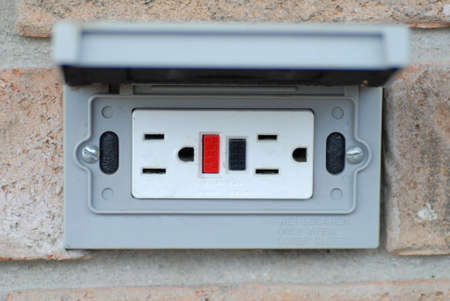 grounded outdoor electrical socket on brick wall