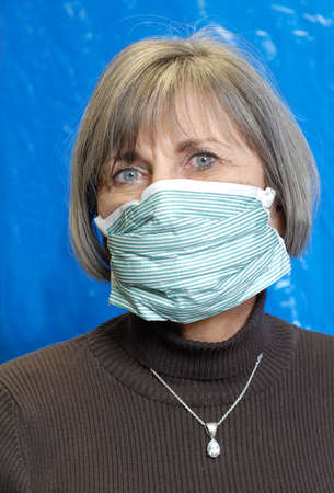 attractive senior woman wearing protective medical mask Stock Photo