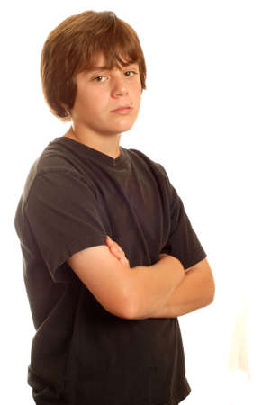 upset young teenage boy standing with his arms crossed
