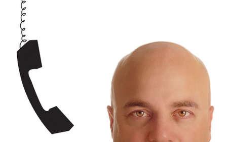 head of bald man with phone receiver dangling beside his ear Stock Photo