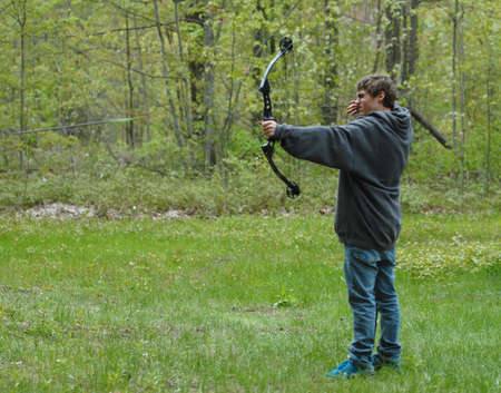 teenage boy shooting compound bow with arrow in the scene Stock Photo