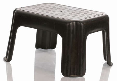 black step stool with reflection on white background