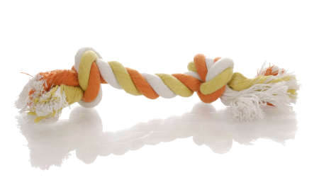 orange and yellow dog tug rope toy with reflection on white background Фото со стока