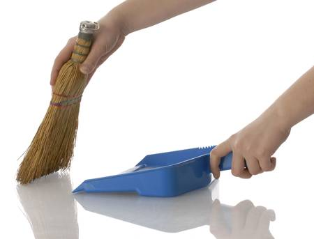hands holding broom and dust pan sweeping up with reflection