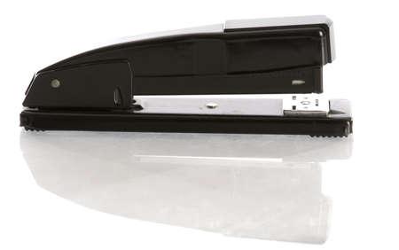 office stapler: black office stapler with reflection on white background