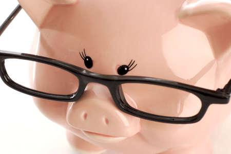 black rimmed: pink piggy bank wearing black rimmed glasses on white background