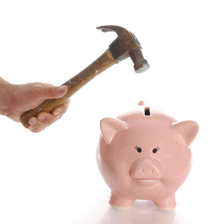 man holding hammer aiming for pink piggy bank money box with reflection on white background Stock Photo