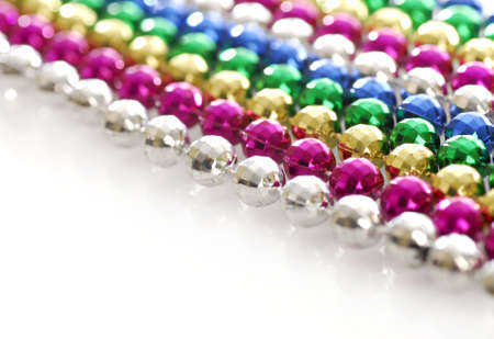 rows of colorful mardi gras beads strung out in a line with reflection on white background photo