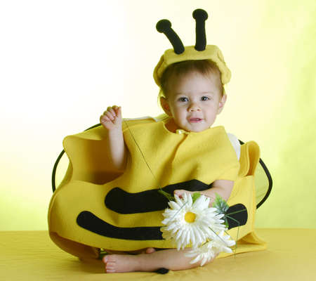 bee on flower: one year old child dressed up like a bee on yellow background