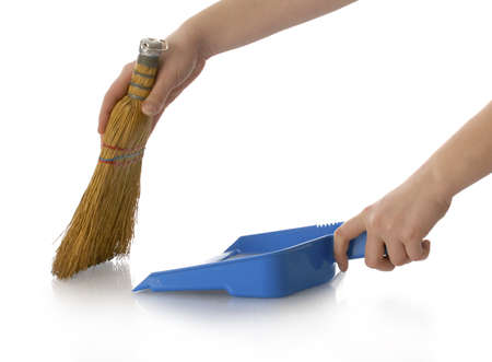 sweeping: hands holding broom and dust pan sweeping up with reflection on white background