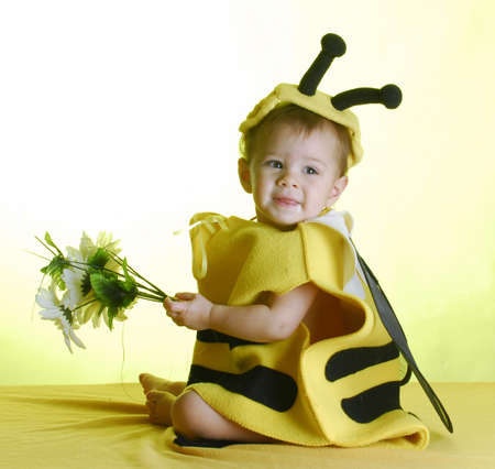 cute baby wearing bee costume on yellow background