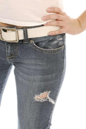 torso of slim woman wearing denim jeans on white background