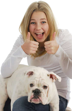 teenage girl giving thumbs up with her dog on her lap on white background