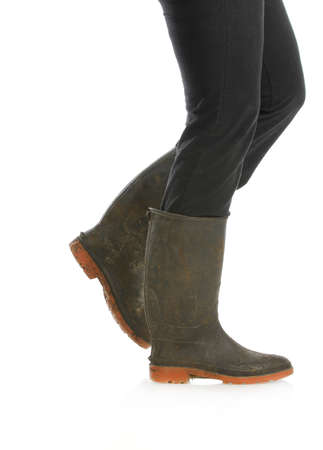 muddy boots - woman walking with muddy boots on white background photo