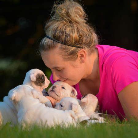 Mujer que juega en la hierba con camada de cachorros Foto de archivo - 42895201