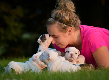 Mujer que juega en la hierba con camada de cachorros Foto de archivo - 42895202