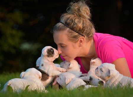 Mujer que juega en la hierba con camada de cachorros Foto de archivo - 58340465