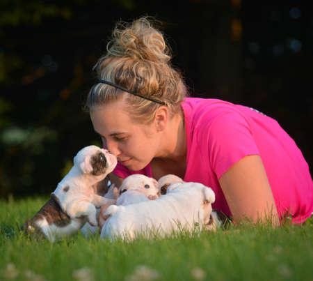 Mujer jugando con camada de cachorros de bulldog inglés fuera Foto de archivo - 65616044