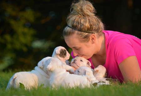 Mujer jugando con camada de cachorros de bulldog inglés fuera Foto de archivo - 65616050