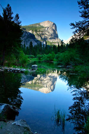 Reflection of the North Dome plays on the clear waters of the beautiful Mirror Lake Stock Photo - 614321