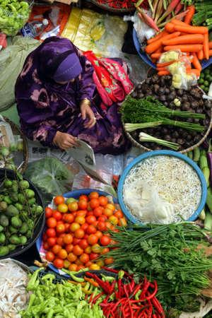 코타 Bharu 말에서 시장에서 신선한 야채를 파는 회교도 여자