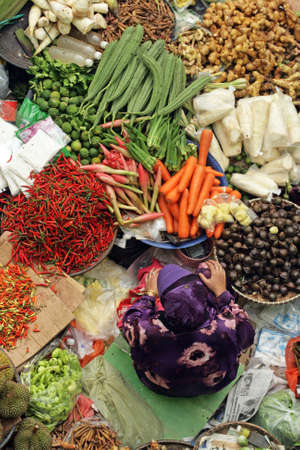asian produce: Muslim woman selling fresh vegetables at market in Kota Bharu Mal