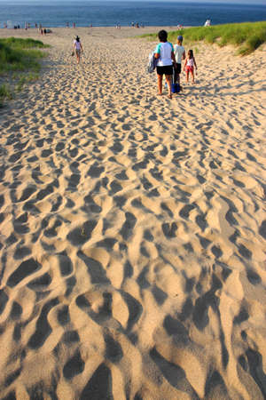 Cape Cod is an arm-shaped peninsula nearly coextensive with Barnstable County, people walking to the beach photo