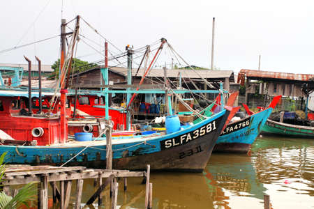 Colorful chinese fishing boat resting at a Chinese Fishing Village, Sekinchan, Malaysia
