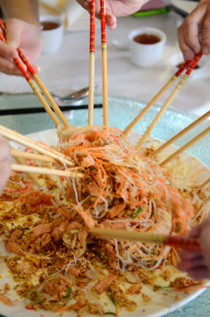 chop sticks: A group of people mixing and tossing Yee Sang dish with chop sticks. Yee Sang is a popular delicacy taken during Chinese New Year, believed to bring good fortune and luck Stock Photo