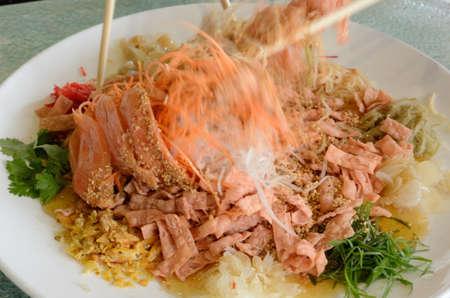 manjar: Un grupo de personas de mezcla y lanzando Yee Sang plato con palillos. Yee Sang se toma un manjar popular durante el Año Nuevo Chino, que se cree que trae buena fortuna y suerte