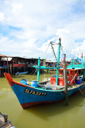 Colorful chinese fishing boat resting at a Chinese Fishing Village- Sekinchan, Malaysia