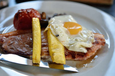 Grilled pork steak with egg on top