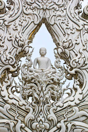 White Buddha sits  deep in meditation with white ray photo