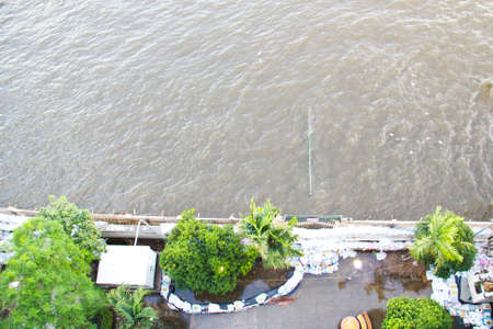 BANGKOK, THAILAND - OCTOBER 25: A group of sandbags are laid in front of pier which sinks in Chao phraya river in  Siriraj hospital for flooding prevention on October 25, 2011 in Bangkok, Thailand