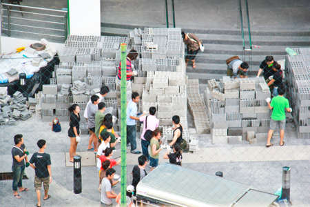 BANGKOK, THAILAND - OCTOBER 25: A group of Thai people help carry brick for flooding prevention at Siriraj hospital on October 25, 2011 in Bangkok, Thailand