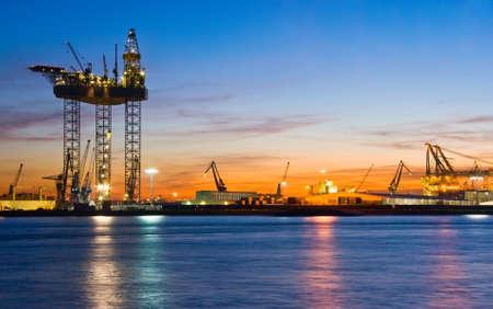 Big drilling platform in repair in the harbour at sunset