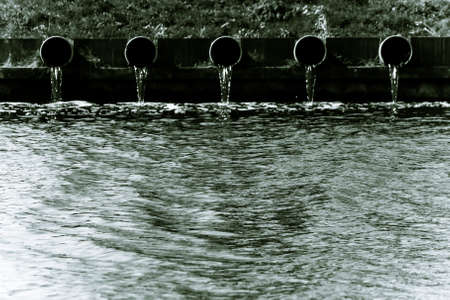 Black and white image, drain-pipes with streaming water