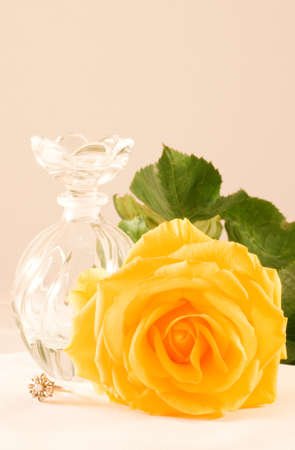 Yellow rose with green leaves, small glass bottle, diamond ring photo
