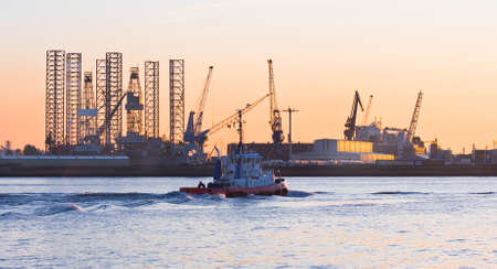 shiprepair: Ship-repair industry and tugship passing by on the river