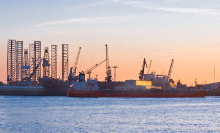 shiprepair: Ship-repair industry at sunset with ship passing by on the river