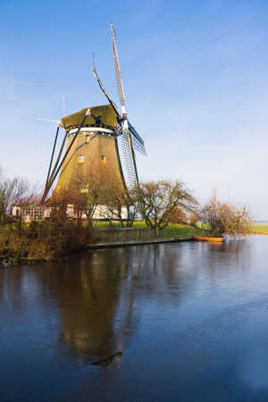 Dutch windmill in sunny frozen polder landscape photo
