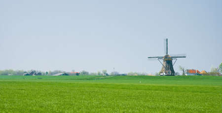 polder: Dutch polder landscape with mill and farms on the dike Stock Photo