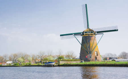Dutch mill in polder with man turning the wings into the wind Stock Photo - 4694463