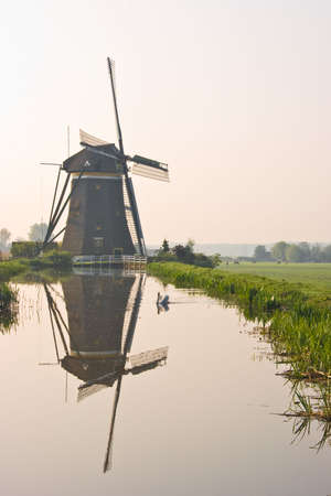 watermills: Dutch watermill at the waterside with reflection after sunrise