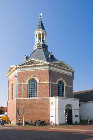 octagonal: Dutch village church in the morning sun with blue sky Stock Photo