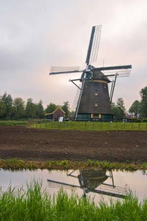 watermills: Dutch mill, build anno 1621, in farmland on cloudy morning Stock Photo