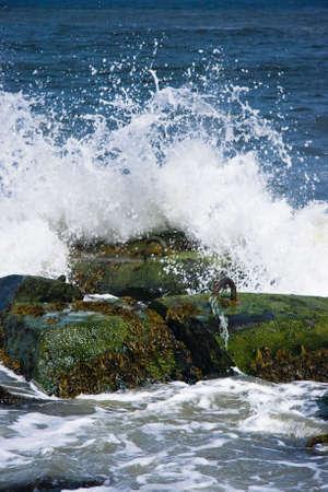 Breakers op basalt stenen aan de kust op zonnige dag