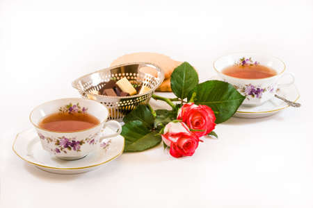 Two cups of tea with chocolates, cookies and red roses  photo